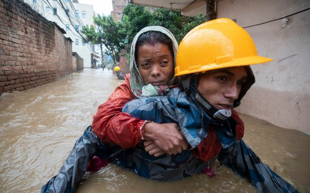 A rescuer carries a woman from flooded houses following torrential rains in Kathmandu, Nepal, 12 July 2019. Meteorologists warned of heavy monsoon rains in Nepal that put several parts of the country at risk of floods and landslides. (Photo by Narendra Shrestha/EPA/EFE/Rex Features/Shutterstock)