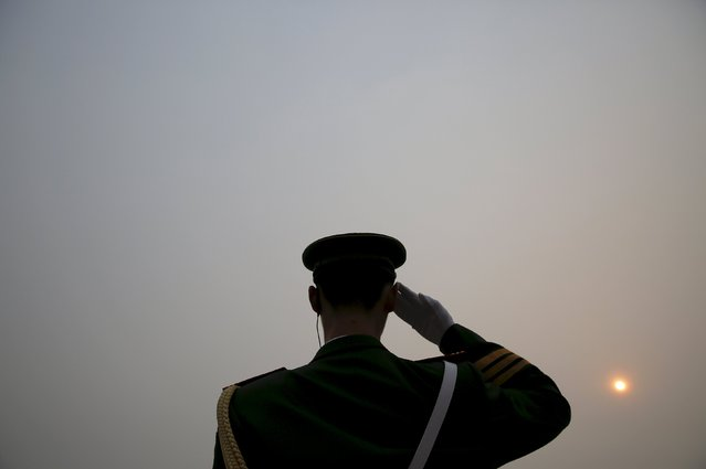 The sun is seen through smog on a severely polluted day as a paramilitary policeman salutes to delegates arriving at the Great Hall of the People before the opening ceremony of the National People's Congress (NPC) in Beijing, China, March 4, 2016. (Photo by Damir Sagolj/Reuters)