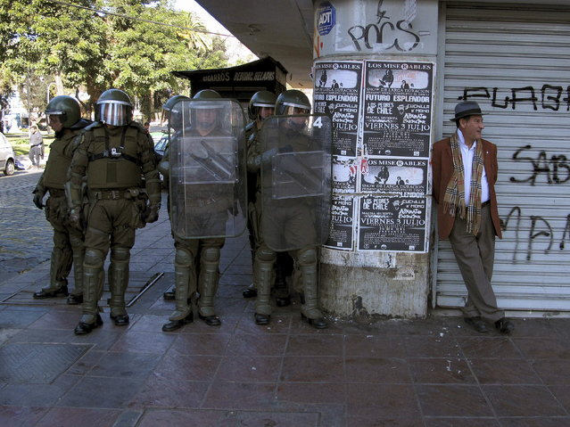 A man takes a break as riot policemen stand guard during a protest to demand changes in the Chilean education system in Valparaiso city, Chile June 25, 2015. (Photo by Lucas Alvarado/Reuters)