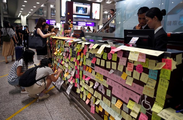 "An information counter is seen covered with post-it notes as part of the ""Lennon Wall"" movement during a protest against the recent violence in Yuen Long, at Hong Kong airport, China on July 26, 2019. At the airport protesters, many dressed in black and seated on the ground, gradually filled the entire arrivals hall. They held up signs calling on the government to withdraw the extradition bill completely, while chants of ""Free Hong Kong"" reverberated around the cavernous glass and steel hall. (Photo by Edgar Su/Reuters)"