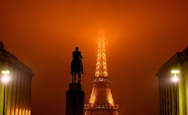 A picture taken on January 24, 2017 in Paris shows the statue of the Marshal Foch at the Trocadero, with a view of the top of the Eiffel Tower hidden by the fog in the background. (Photo by Franck Fife/AFP Photo)