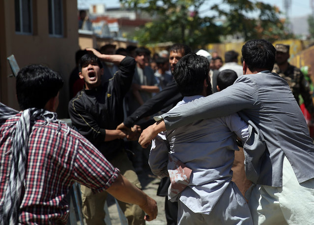Afghan civilians react at the site of a suicide attack on a NATO convoy in Kabul, Afghanistan, Tuesday, June 30, 2015. (Photo by Massoud Hossaini/AP Photo)
