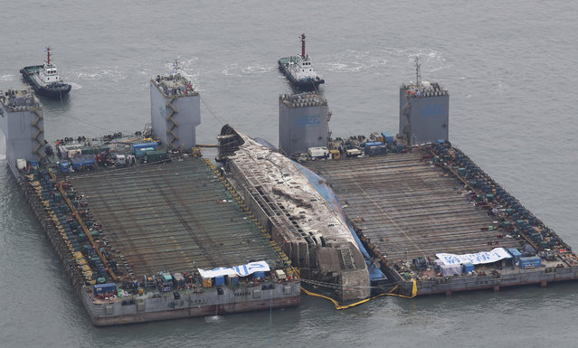 The partially lifted sunken ferry Sewol, center, is ready for transport in waters off Jindo, South Korea, Friday, March 24, 2017. South Korean efforts to bring a sunken, 6,800-ton ferry back to land cleared an obstacle on Friday after divers cut off a vehicle ramp that had been dangling from the ship and hindering efforts to raise it. (Photo by Suh Myung-gon/Yonhap via AP Photo)