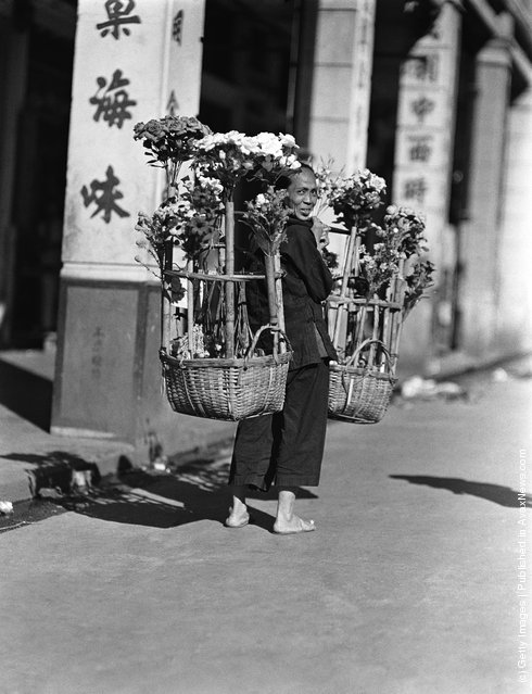 1920s: Female paper flower vendor carrying two large baskets of artificial flowers, Hong Kong