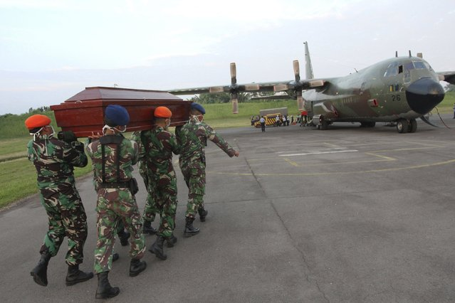 Indonesian air force soldiers carry the coffin of a victim of an Indonesian military C-130B Hercules aircraft that crashed into a residential area to another cargo plane for transport home at a military airbase in Medan, North Sumatra, Indonesia July 2, 2015 in this photo taken by Antara Foto. (Photo by Irsan Mulyadi/Reuters/Antara Foto)