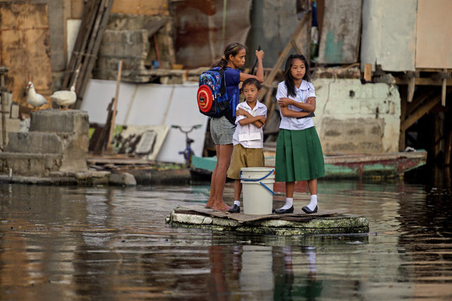 Elementary students, living on flooded Artex Compound, ride on makeshift boat to attend the first day of school in Panghulo 1 Elementary School in Malabon, north of Manila on June 3, 2019. Twenty three million students will be trooping back to their respective schools nationwide. (Photo by Noel Celis/AFP Photo)