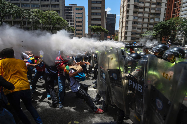 Venezuela's opposition activists clash with riot police agents during a protest against Nicolas Maduro's government in Caracas on April 4, 2017. (Photo by Juan Barreto/AFP Photo)