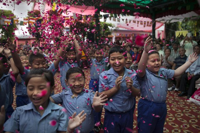 Exiled Tibetan school children throw flowers in the air as they sing a birthday song to celebrate their spiritual leader, the Dalai Lama's' 80th birthday in New Delhi, India, Monday, July 6, 2015. (Photo by Tsering Topgyal/AP Photo)