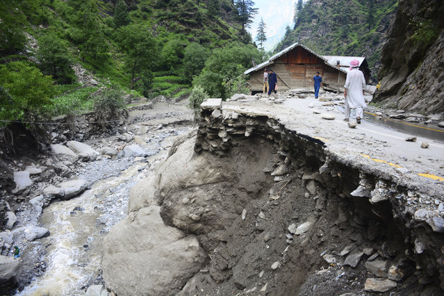 Villagers walk along a road washed away by heavy flooding in Neelum Valley of Pakistani controlled Kashmir, Monday, July 15, 2019. Pakistan says many people are missing and feared dead after heavy rains triggered flash floods in Pakistani-controlled Kashmir. Ahmed Raza Qadri, the Pakistani minister for disaster management in the disputed territory, says the flooding late on Sunday also caused much destruction and damage in the village of Lesswa in Neelum Valley. (Photo by M.D. Mughal/AP Photo)