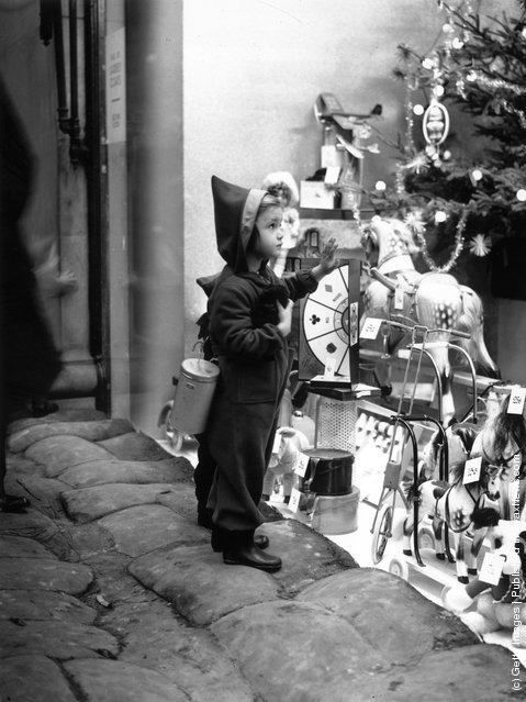 1939: A seasonably attired young shopper climbs on to the sandbags to get a closer look at the toys in a shop window in the West End of London