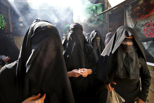 This picture taken on Tuesday, October 11, 2016, shows veiled Iranian women taking part in a mourning ceremony for Ashoura, as they cover their faces symbolically, in the city of Khorramabad, southwest of the capital Tehran, Iran. Shiites mark Ashoura, the tenth day of the Muslim month of Muharram, to commemorate the martyrdom of Imam Hussein, a grandson of Prophet Muhammad and one of Shiite Islam's most beloved saints, during the 7th century Battle of Karbala in present-day Iraq. (Photo by Ebrahim Noroozi/AP Photo)