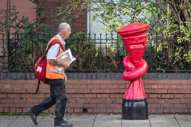 "A postman walks past an art work titled ""Alphabetti Spaghett"" by artist Alex Chinneck on Norborough Road in Sheffield, Yorkshire, England on September 26, 2019. (Photo by Danny Lawson/PA Images via Getty Images)"