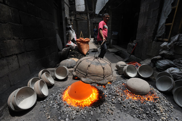 A man uses a traditional way to produce a pot at a workshop in Zhijin, Guizhou Province, China, May 1, 2016. (Photo by Reuters/Stringer)