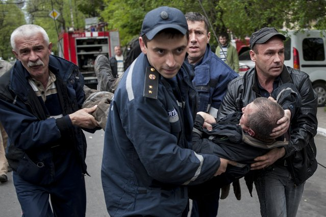People carry a firefighter injured during an attack at a police station in Mariupol, eastern Ukraine, Friday, May 9, 2014. Fighting between government forces and insurgents in Mariupol has left several people dead. (Photo by Evgeniy Maloletka/AP Photo)