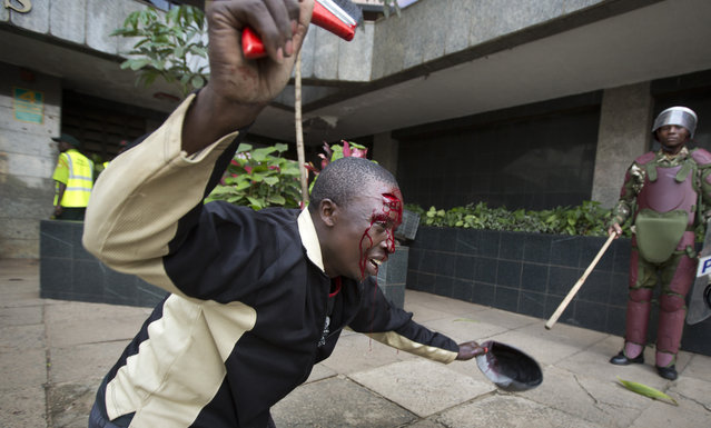 An opposition supporter with a head wound crawls on his knees past riot police, begging them not to beat him, during a protest in downtown Nairobi, Kenya, Monday, May 16, 2016.. (Photo by Ben Curtis/AP Photo)