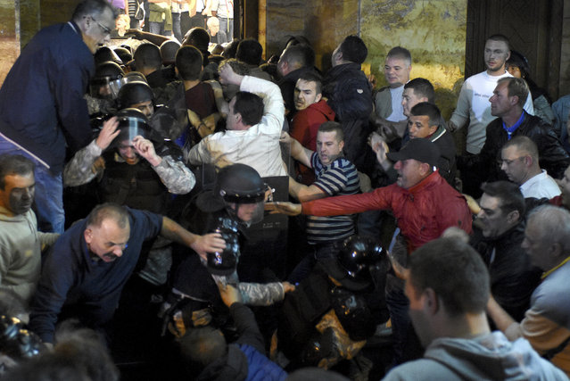 Protestors clash with police to enter into the parliament building in Skopje, Macedonia, Thursday, April 27, 2017. Chaos swept into Macedonia's parliament Thursday as demonstrators stormed the building and attacked lawmakers to protest the election of a new speaker despite a months-old deadlock in efforts to form a new government. (Photo by Dragan Perkovski/AP Photo)