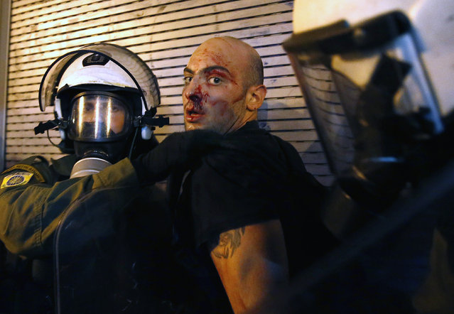 A protester bleeds as he is arrested by riot police following clashes in Athens, Greece July 15, 2015. (Photo by Yannis Behrakis/Reuters)