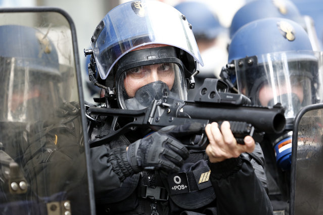 A riot police officer aims during the May Day march, Monday May 1, 2017, in Paris. With just six days until a French presidential runoff that could define Europe's future, far-right leader Marine Le Pen and centrist Emmanuel Macron held high-stakes rallies Monday that overlapped with May Day marches and underscored the fact that jobs are voters' No. 1 concern. (Photo by Kamil Zihnioglu/AP Photo)