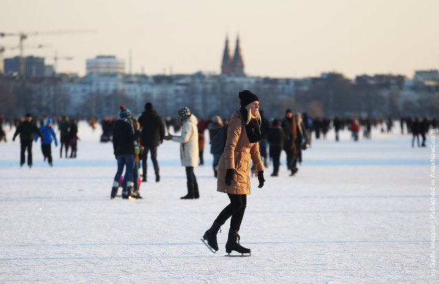 People stay on the frozen Aussenalster river during the 'Alstervergnuegen' on February