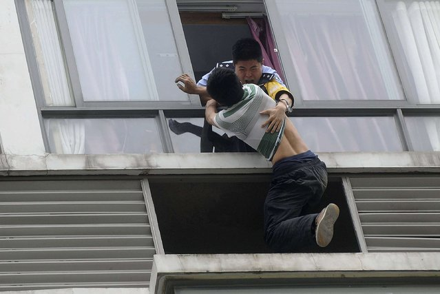 A police officer (top) grabs a man who tries to jump off the seventh floor of a hotel, in Chengdu, Sichuan province May 19, 2014. The32-year-old man attempted to commit suicide on Monday after a failed relationship. Police and his ex-girlfriend managed to talk him down 3 hours later, local media reported. (Photo by Reuters/Stringer)