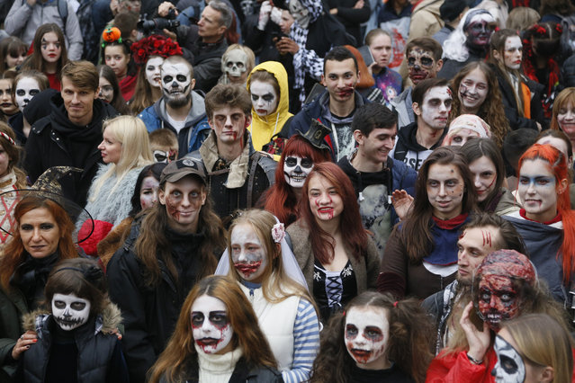 """People dressed as Zombies participate in a """"Zombie Walk"""" on the weekend before Halloween in central Kyiv, Ukraine Saturday, October 26, 2019. (Photo by Efrem Lukatsky/AP Photo)"""