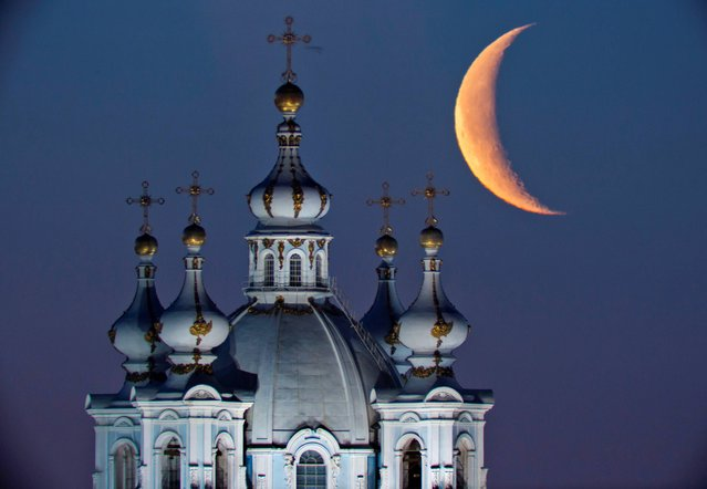 The moon rises in the sky above the domes of the Smolny Cathedral in St.Petersburg, Russia, Friday, April 25, 2014. One of St. Petersburg landmarks, the Smolny convent's main church was built between 1748 and 1764 by Italian architect Francesco Bartolomeo Rastrelli. (Photo by Dmitry Lovetsky/AP Photo)