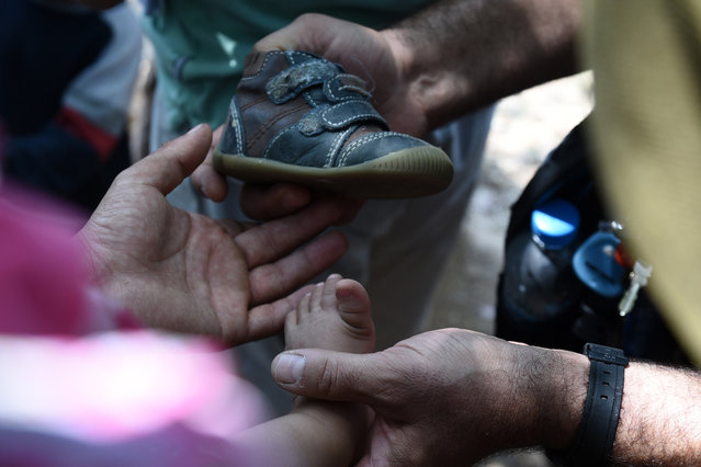 "Afghan refugees prepare to fit a shoe distributed by the ""Solidarity For All"" on a child's foot, in the Pedion tou Areos park in central Athens, on Friday, July 24, 2015. (Photo by Giannis Papanikos/AP Photo)"