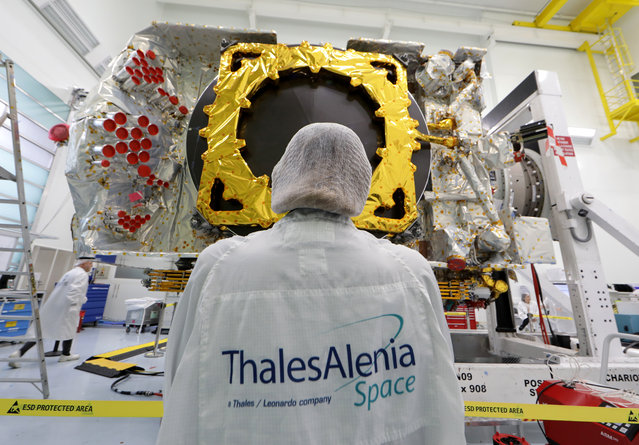 A technician stands in front of the all-electric Konnect communications satellite, which will be shipped to the Guiana Space Center in Kourou, in the clean room facilities at the Thales Alenia Space plant in Cannes, France, November 22, 2019. (Photo by Eric Gaillard/Reuters)