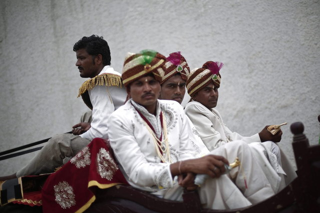 Grooms arrive in a horse cart to attend a mass wedding ceremony at Ramlila ground in New Delhi June 15, 2014. A total of 92 physically challenged couples of all religions from across India took their wedding vows on Sunday during the mass wedding ceremony organised by a non-governmental organisation (NGO), organisers said. (Photo by Adnan Abidi/Reuters)