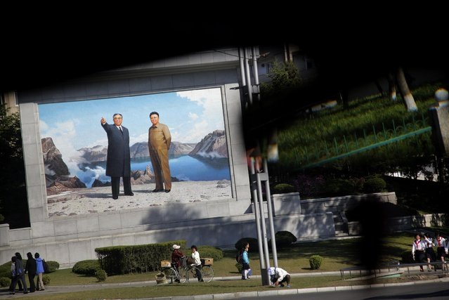 A portrait of the late leaders, Kim Il Sung, left, and Kim Jong Il, right, stands on a street corner as seen through a car windscreen, Monday, May 4, 2015 in Pyongyang, North Korea. (Photo by Wong Maye-E/AP Photo)