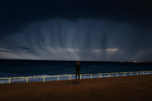 A man looks at a thunderstorm above the Mediterranean sea on the French Riviera city of Nice, on October 23, 2019. The Bouches-du-Rhone, Var and Vaucluse departments were placed on orange alert joining six other departments in the south of France following flooding overnight which closed some road networks along the coast and which also forced some people to evacuate their homes. (Photo by Valery Hache/AFP Photo)