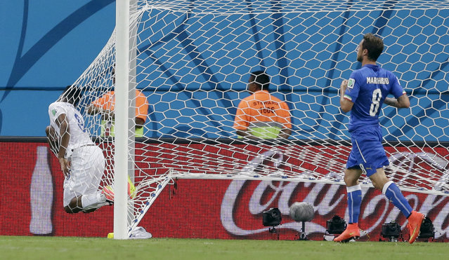 England's Daniel Sturridge, left, lands in the back of the net after missing a chance during the group D World Cup soccer match between England and Italy at the Arena da Amazonia in Manaus, Brazil, Saturday, June 14, 2014. Defending at right is Italy's Claudio Marchisio. (Photo by Matt Dunham/AP Photo)
