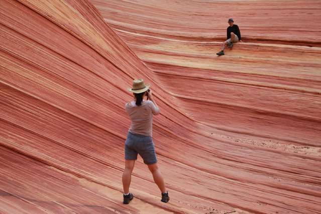 In this May 28, 2013, file photo, a hiker takes a photo on a rock formation known as The Wave in the Vermilion Cliffs National Monument in Arizona. The richly colored geological upheaval along the Arizona-Utah border is one of the most sought-after hikes in the West. But the Wave isn't without dangers that led officials with the U.S. Bureau of Land Management to implement a series of safety measures following a trio of deaths in 2013. (Photo by Brian Witte/AP Photo)