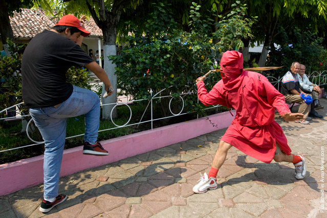 An actor dressed as a demon whips a resident during a ceremony as part of religious activities to mark the start of Holy Week in Texistepeque, Santa Ana, El Salvador on April 18, 2011. Participants receive lashes from the actors, also know as Talciguines, as punishment for their sins