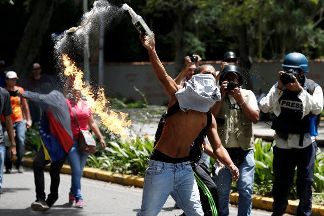 A demonstrator throws a molotov cocktail against riot policemen during a protest called by university students against Venezuela's government in Caracas, Venezuela, June 9, 2016. (Photo by Carlos Garcia Rawlins/Reuters)