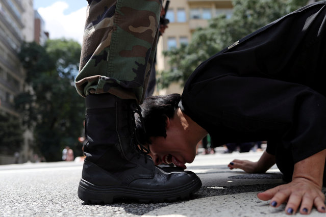 """Venezuelan artist Deborah Castillo licks the boots of a man dressed as a member of the military during her performance """"Lamebrasil, Lamezuela – questioning power in Latin America"""", in Sao Paulo, Brazil, March 24, 2019. (Photo by Amanda Perobell/Reuters)"""