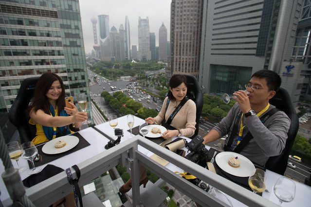 "Diners are suspended from a crane as they enjoy a meal organized by the ""Dinner in the Sky"" over Lujiazui Financial District in Shanghai on June 27, 2014. (Photo by AFP Photo/Stringer)"