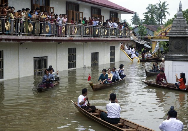 Myanmar opposition leader Aung San Suu Kyi, center, rides a boat as she leaves after visiting a monastery where flood victims are sheltered in Bago, 80 kilometers (50 miles) northeast of Yangon, Myanmar, Monday, August 3, 2015. A report issued Saturday by the U.N. Office for the Coordination of Humanitarian Affairs cited Myanmar disaster officials estimating that more than 156,000 people had been affected by flooding. (Photo by hin Maung Win/AP Photo/)