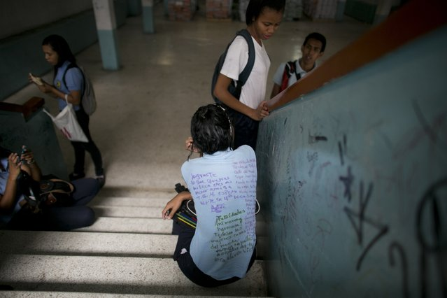 In this May 31, 2016 photo, a student's uniform shirt is covered with messages that were hand written by classmates, an end-of-the-year school ritual, at a public high school in Caracas, Venezuela. A quarter of Venezuelan children missed some school this year because of hunger, according to the local nonprofit Foundation Bengoa. (Photo by Ariana Cubillos/AP Photo)