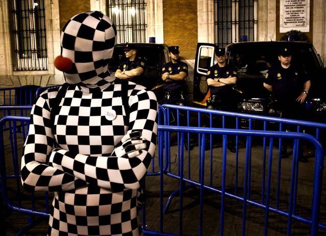 A demonstrator dressed in a chess board costume performs next to police officers during a protest at Puerta del Sol plaza in Madrid