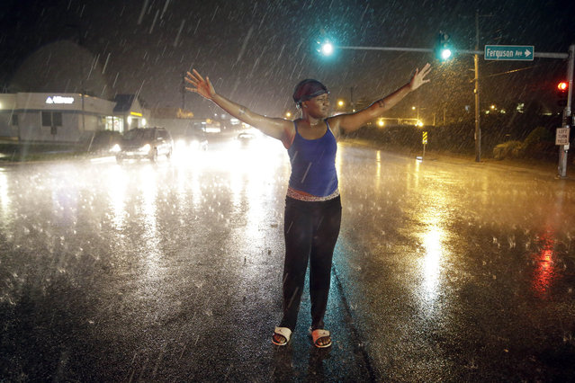 A protester stands in the rain while marching, Sunday, Aug. 9, 2015, in Ferguson, Mo. Sunday marks one year since Michael Brown was shot and killed by Ferguson Police Officer Darren Wilson. (Photo by Jeff Roberson/AP Photo)