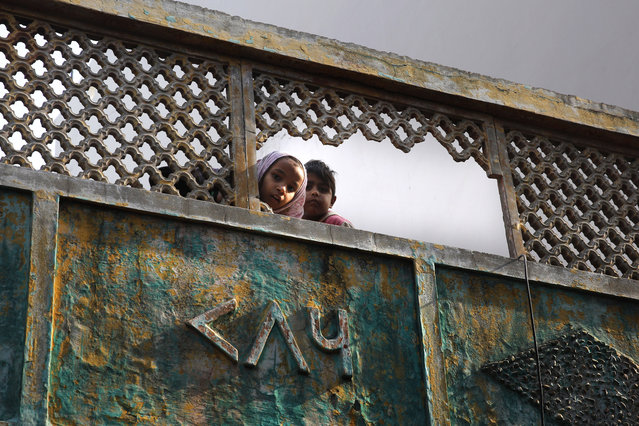 In this Tuesday, December 24, 2019, photo, Muslim children look through broken fencing of their balcony in a congested neighborhood where five people died allegedly in police firing during protests against Citizenship Amendment Act, in Meerut, India. Tens of thousands of people have taken to the streets to oppose a new law that grants a path to citizenship for immigrants of every religion except Islam. Many say the law, passed by Prime Minister Narendra Modi's Hindu-nationalist government, discriminates against Muslims and undermines the country's secular foundations. (Photo by Rajesh Kumar Singh/AP Photo)