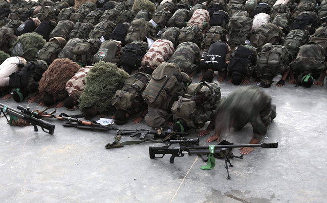 Palestinian fighters of Ezz Al-Din Al-Qassam militia, the military wing of the Hamas movement, pray next to their weapons after their parade in the streets of Beit Hanun in the northern Gaza Strip, 11 August 2015. (Photo by Mohammed Saber/EPA)