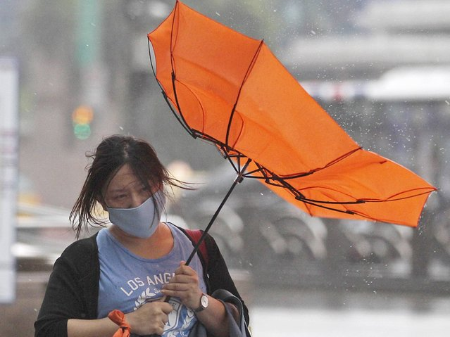 A woman holds her umbrella while walking against strong winds as Typhoon Matmo hits Taiwan, on Jule 23, 2014. (Photo by Pichi Chuang/Reuters)