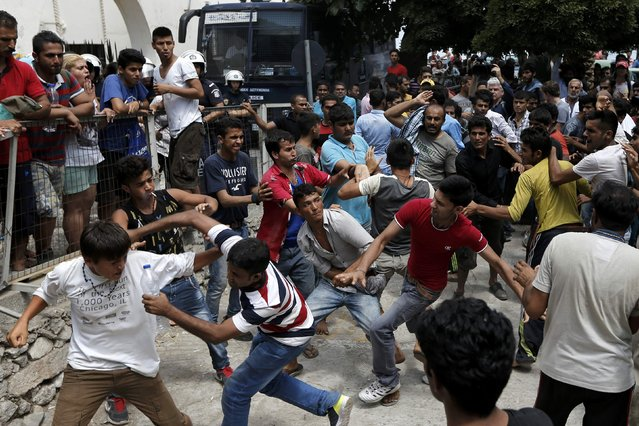 Pakistani, Iranian and Afghani migrants scuffle outside the police station of the city of Kos over priority at a registration queue on the Greek island of Kos, August 15, 2015. (Photo by Alkis Konstantinidis/Reuters)