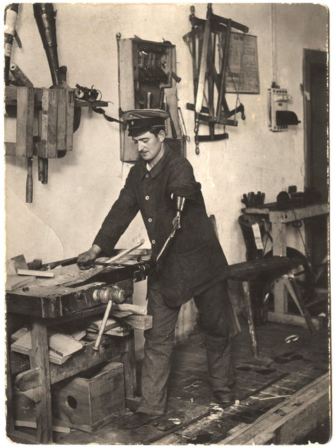 A German soldier works on shaving a piece of wood with a prosthetic limb for his left arm. (Photo by Dr. P.A. Smithe/National World War I Museum, Kansas City, Mo.)