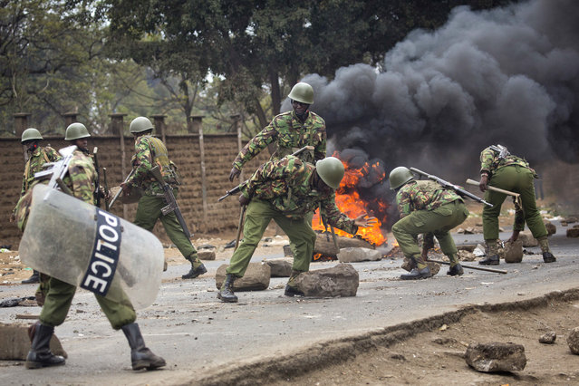 Kenyan security forces remove stones from a street blocked by supporters of Kenyan opposition leader and presidential candidate Raila Odinga who demonstrate in the Mathare area of Nairobi Wednesday , August 9, 2017. (Photo by Jerome Delay/AP Photo)