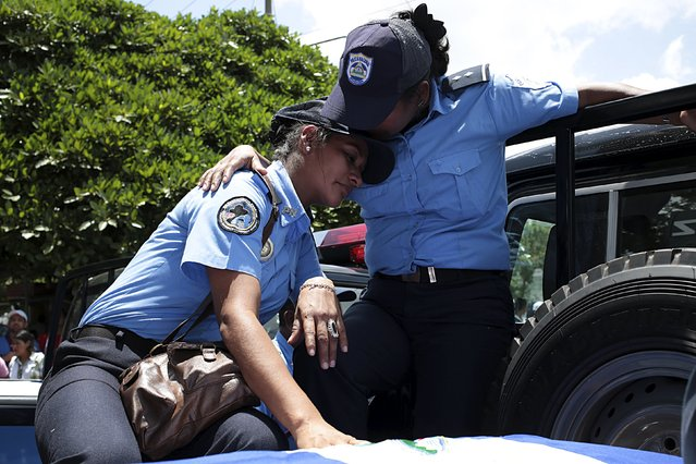 Policewomen mourn during a posthumous tribute for five policemen in Managua, Nicaragua August 18, 2015. (Photo by Oswaldo Rivas/Reuters)