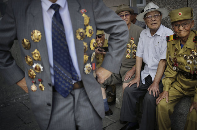 North Korean war veteran, Kim Hak Chol, 81, a retired soldier, right, together with other veterans decorated with medals, attend a parade to celebrate the anniversary of the  Korean War armistice agreement, Sunday, July 27, 2014, in Pyongyang, North Korea. North Koreans gathered at Kim Il Sung Square as part of celebrations for the 61st anniversary of the armistice that ended the Korean War. (Photo by Wong Maye-E/AP Photo)