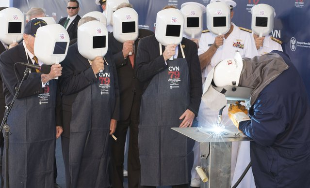 Ceremony participants watched as Newport News Shipbuilding Welder Leon Walston welded the initials of Caroline Kennedy, ship's sponsor for the aircraft carrier John F. Kennedy (CVN 79), during the keel-laying ceremony at Newport News Shipbuilding yard in Newport News, Virginia August 22, 2015. (Photo by Ricky Thompson/Reuters/Huntington Ingalls Industries)